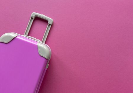 Pink plastic suitcase on pastel paper background.Travel concept holiday summer adventure trip. Flat lay with one simple thing. Stock photo. 版權商用圖片