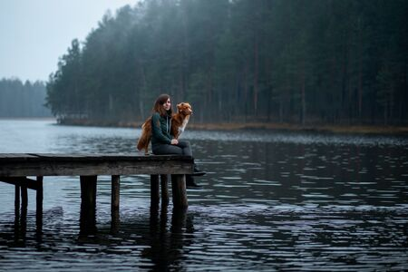 girl with a reddog sit on a pier on the lake. Nova Scotia Duck Tolling Retriever with a man on nature Stock Photo