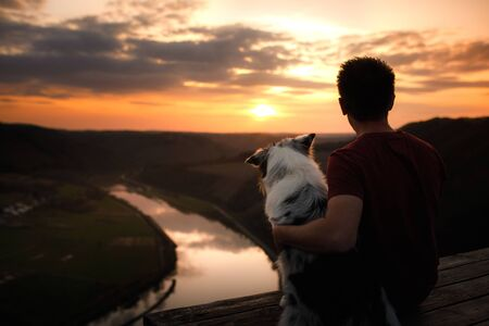 A man with a dog at sunset. walk with a pet. Australian Shepherd and owner in nature look at a beautiful view