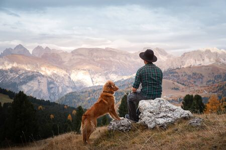 man in Hat with a dog in the mountains valley. Nova Scotia Duck Tolling Retriever with a people. men sit on a stone near a cliff