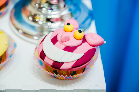 delicious cupcake with decorations of smiling Cheshire cat