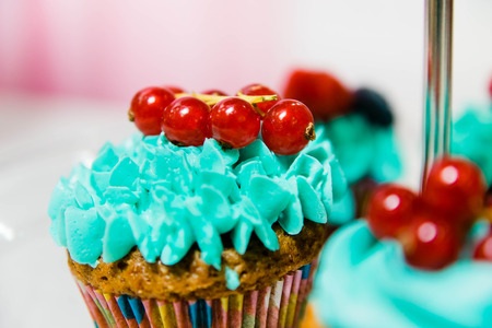 a delicious cupcake with blue cream and red currant close up 免版税图像