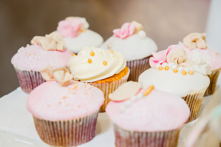 some cupcakes with white and pink cream and golden sparkles 免版税图像