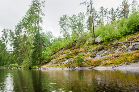 low stony shore coming to the water of Karelian lake