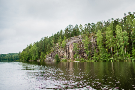 calm lake and rocky shore with forest