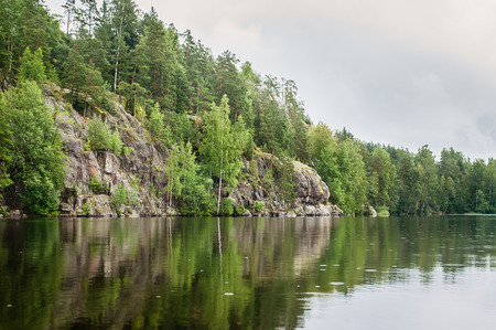 calm lake and rocky shore with trees