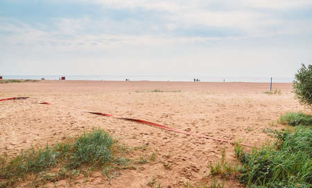 A deserted closed sandy beach. Empty coast of the sea resort in Russia