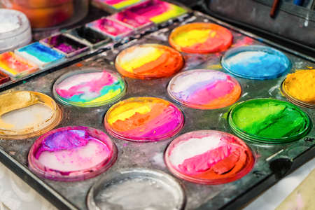 Colored paints and eyeshadow for children's makeup. Creative set for applying cosmetics to the face.