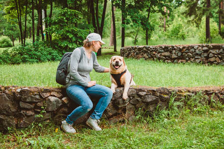 A girl with a backpack is sitting on the lawn stroking a Labrador Retriever and smiling. Outdoor recreation with a dog