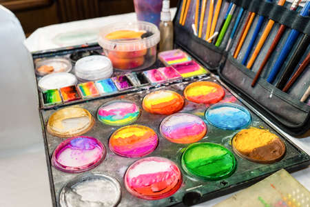 Colored paints and brushes for children's makeup. Creative set for applying cosmetics to the face.