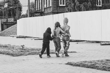 Three children walk in the street with their arms around each other. Friendship of two boys and a girl