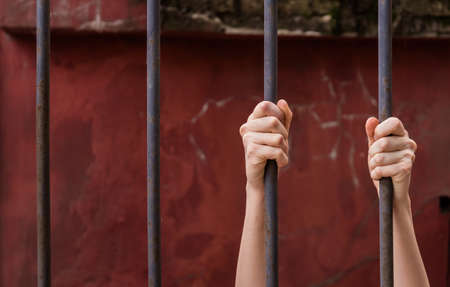 The girl's hands are held by metal bars. Symbol of violation of women's rights. Background