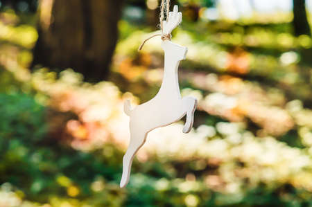 A wooden figure of a deer is suspended from a tree. Accessories, toys and decor handmade in rustic style