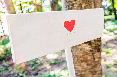 A wooden white signboard with a heart drawn on it. Decoration of the holiday in the open air in the rustic style 스톡 콘텐츠