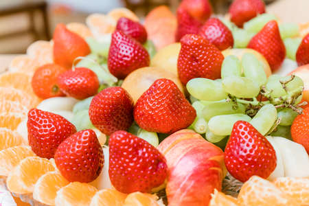 A plate with strawberries, oranges, apples and grapes. Fruit assortment for the dining table