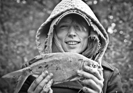 a smiling girl holding a freshly caught fish