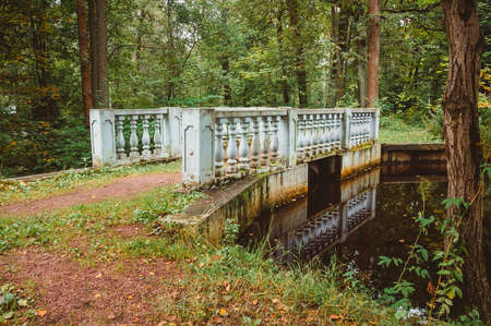 A small bridge with balusters over a stream in the forest. The architecture of the 19th century in the classicism style