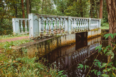 A small bridge with balusters across the stream in the garden on the territory of a noble estate. Nineteenth-century architecture in the classicism style.