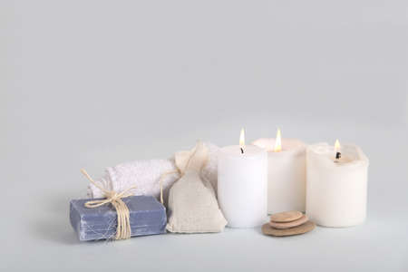Three white candles with the face towel and lavander soap, grass pouch and special stones for massage.