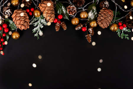 Golden garland, forest pinecones, red berries and green leaves in snow on the black background with multicoloured lights.