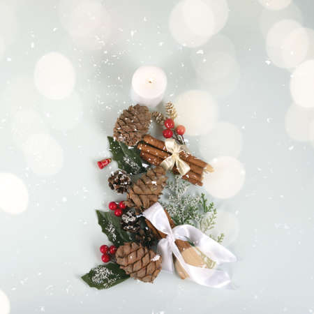 White candle, forest pinecones, red berries and green leaves with festive cinnamon sticks in a form of a New Year tree in snow and golden lights.