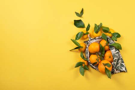 Fresh, fruity mandarins in green and reusable bag.
