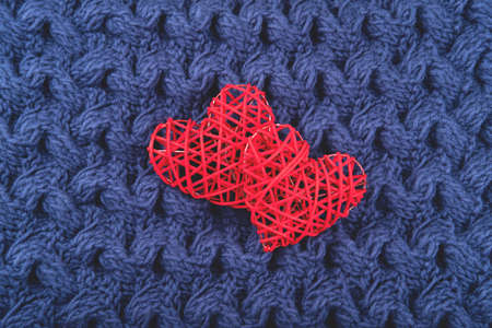 Two beautiful red hearts on the blue knit background. St Valentine's concept with copy space. Foto de archivo - 138476716