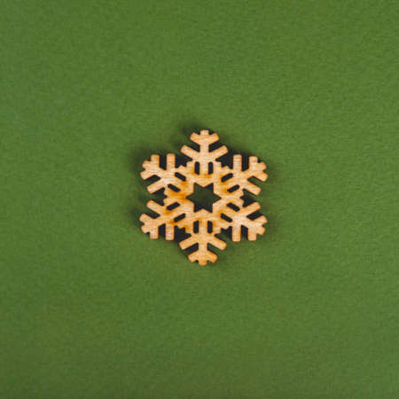 The zero waste and minimalist new year concept as the handmade wooden snowflake on the green background.
