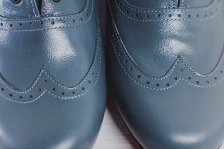 Stylish gray mans crafted shoes for ballroom dancing with laces from skin and suede on the wooden background. photography of mens gray boots for ballroom dancing. macro top view