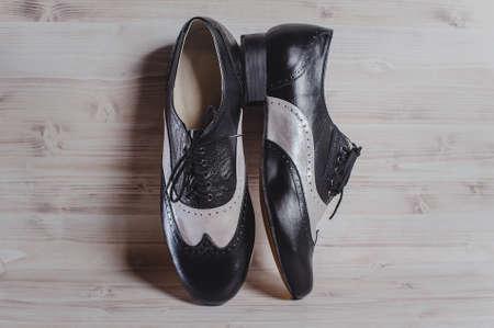 Eleganti scarpe artigianali nere e grigie per balli da sala realizzati in vera pelle su fondo di legno. fotografia di stivali da uomo neri e grigi per