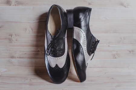 Stylish black and gray mans crafted shoes for ballroom dancing made of genuine leather on the wooden background. photography of mens black and gray boots for ballroom dancing. Stock Photo