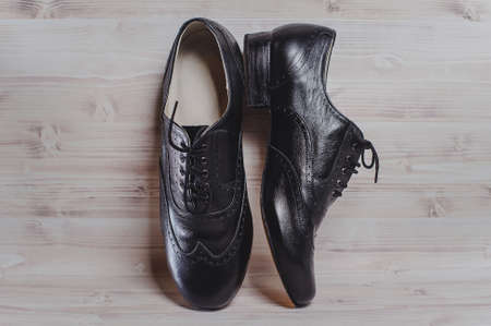Stylish black mans crafted shoes for ballroom dancing with laces from skin and suede on the wooden background. photography of mens black boots for ballroom dancing. Stock Photo