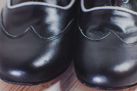 Stylish black with a gray stripe mans crafted shoes for ballroom dancing made of genuine leather on the wooden background. mens black with a gray stripe boots for ballroom dancing. macro view close