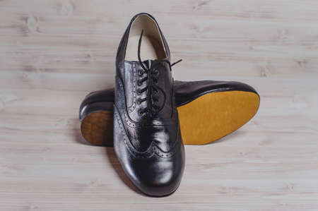 Stylish black mans crafted shoes for ballroom dancing with laces from skin and suede on the wooden background. photography of mens black boots for ballroom dancing. in front view
