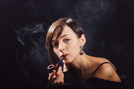 The brunette in a black sweatshirt is smoking a pipe in a cloud of smoke. portrait view closeup Banco de Imagens