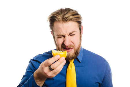 Handsome businessman in a blue business suit standing isolated against white background eats a lemon, frowns and squintes from sour close Фото со стока