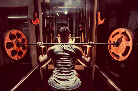Cross training. Part of young man in sportswear lifting barbell at gym. Toned image. Young man crouches with a barbell. With a barbell on the shoulders. At the moment of squatting. back view close up Stock Photo