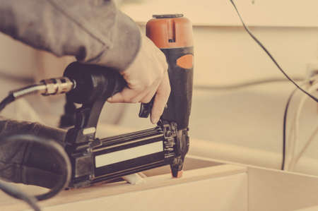 Man collects furniture details in the carpentry shop. Toned image. Uses a professional stapler or nail gun. close up view Stock Photo