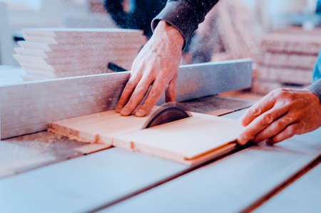 A carpenter works on woodworking the machine tool. Toned image. Man collects furniture boxes. Saws furniture details with a circular saw. Process of sawing parts in parts