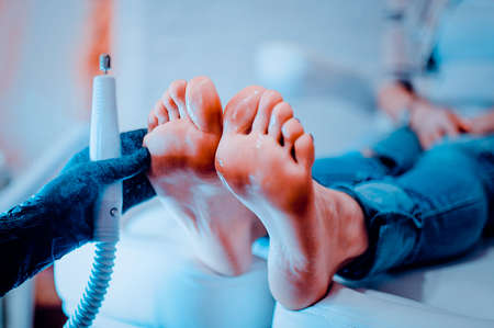 The process of pedicure in a professional beauty salon. Toned image. hardware processing of toes. Care of the skin of the feet Фото со стока - 95590925
