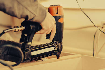 Man collects furniture details in the carpentry shop. Toned image. Uses a professional stapler or nail gun. close up view 写真素材