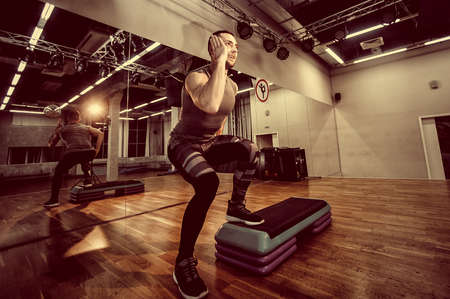 Man doing step up jumps in health club. Toned image. The man is exercising on the stepper. doing steps Фото со стока