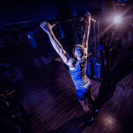 Athlete muscular fitness male model pulling up in a gym. Toned image. Man pulls himself up on the crossbeam. from behind