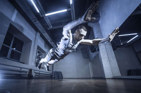 Attractive muscular man doing push-ups on a wooden floor. Toned image. from the side view during a jump close