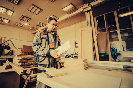 A carpenter works on woodworking the machine tool. Carpenter working on woodworking machines in carpentry shop. Toned image. Man collects furniture boxes. in the front view Фото со стока