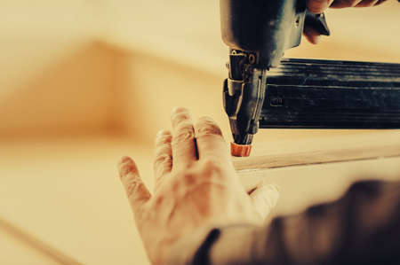 Man collects furniture details in the carpentry shop. Toned image. Uses a professional stapler or nail gun. close up another view Stock Photo
