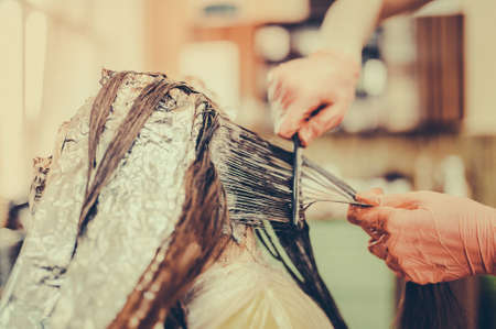 Woman in gloves is dying hair. hair dyeing. Toned image. Hair in foil. combs her hair
