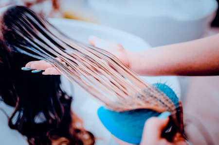 girl in a beauty salon. wash your hair, hair care, health. Toned image. Combing of washed hair with a special comb in the hairdressers. Stock Photo
