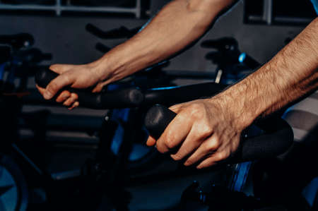 The guy is engaged in a bicycle simulator in the gym. Toned image. The guy is exercising on a stationary bike. hands view