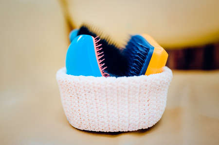 Basket with combs and round hair brushes. Toned image. Comb for combing raw hair in a basket in a hair salon. close up view